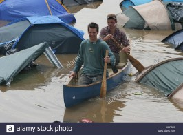 two-men-canoeing-around-the-flooded-pennard-hill-campsite-glastonbury-ABF8H9.jpg